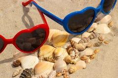 Tas des coquilles et des lunettes de soleil sur le sable à la plage Photo stock
