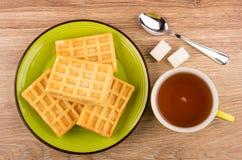 Tas des gaufres dans le plat, tasse de thé, sucre Image stock