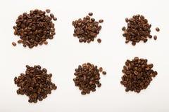 Tas des grains de café bruns d'isolement sur le blanc Photo libre de droits