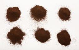 Tas des haricots bruns de cafè moulu d'isolement sur le blanc Photographie stock libre de droits