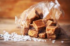 Tas des morceaux de caramel Salted et du sel de mer sur une table en bois Bu photos libres de droits