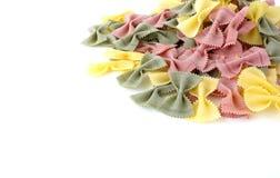 Tas des pâtes multicolores de Farfalle sur le fond blanc Photos libres de droits