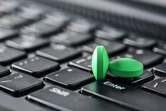 Tas des pilules médicales dans la couleur verte sur le clavier d'ordinateur Sécurité de réseau, protection des données et PC de p Photographie stock