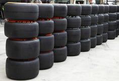 Tas des pneus de véhicule de la formule 1 devant le garage d'arrêt de mine Image stock