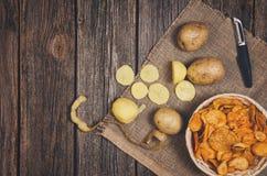 Tas des pommes chips dans la cuvette sur le fond en bois de table image libre de droits