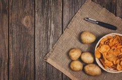 Tas des pommes chips dans la cuvette sur le fond en bois de table photographie stock