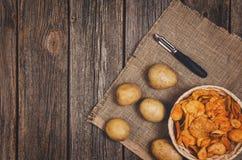 Tas des pommes chips dans la cuvette sur le fond en bois de table image stock