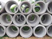 Tas des tuyaux concrets de drainage empilés sur le chantier de construction avec la perspective de diminution Photo stock