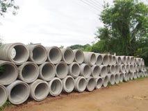 Tas des tuyaux concrets de drainage empilés sur le chantier de construction avec la perspective de diminution Photos stock