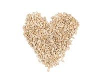 Tas en forme de coeur écossé de graines de tournesol sur le blanc Images libres de droits