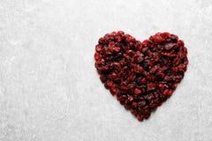 Tas en forme de coeur des canneberges douces sur le fond de couleur, vue supérieure avec l'espace pour le texte Fruits secs images stock