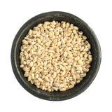 Tas sec cru de grains d'orge perlée dans la cuvette noire de fer Photo stock