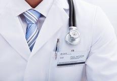 Tasca su un cappotto del laboratorio con un'etichetta e la penna di identificazione di medici fotografie stock