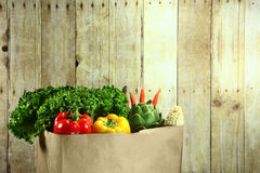 Tasche von Lebensmittelgeschäft-Erzeugnis-Einzelteilen auf einer hölzernen Planke lizenzfreie stockbilder