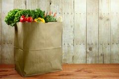 Tasche von Lebensmittelgeschäft-Erzeugnis-Einzelteilen auf einer hölzernen Planke lizenzfreies stockfoto