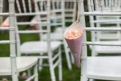 Tasche von rosafarbenen Blumenblättern auf dem chiavari Stuhl Lizenzfreie Stockfotos