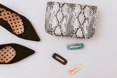 Tasche von snakeskin, von Haarnadeln und von schwarzen Schuhen auf einem beige Pastellhintergrund stockfotografie