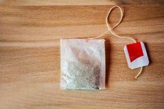 Taschen des grünen Tees auf einem hölzernen Hintergrund Stockfotos
