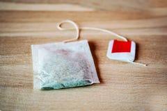 Taschen des grünen Tees auf einem hölzernen Hintergrund Stockbilder