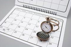 Taschen-Uhr auf Kalender Stockfotos