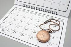 Taschen-Uhr auf Kalender Stockfotografie