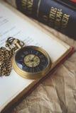 Taschen-Uhr mit alten Büchern auf zerknittertem Papier im Weinlese-Ton Lizenzfreie Stockbilder
