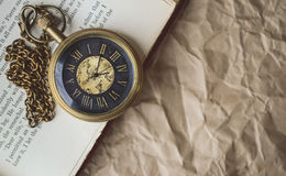 Taschen-Uhr mit alten Büchern auf zerknittertem Papier im Weinlese-Ton Stockfotos