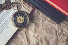 Taschen-Uhr mit alten Büchern auf zerknittertem Papier im Weinlese-Ton Stockfoto
