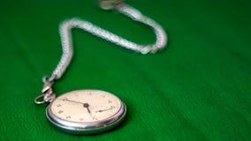 Taschen-Uhr mit Kette auf grünem Hintergrund stockfotografie