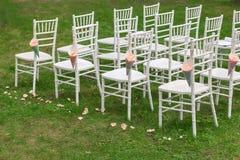 Taschen von rosafarbenen Blumenblättern auf dem chiavari Stuhl Lizenzfreies Stockfoto