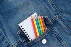 Taschendenimjacke mit einem Notizbuch und farbigen Bleistiften Stockbild