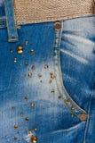 Taschenjeans mit Bergkristallen und Goldgurt Stockbilder