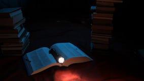 Taschenlampe, die auf dem Buch liegt stock video footage