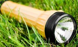 Taschenlampe im Gras Lizenzfreies Stockfoto