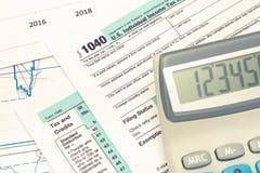 Taschenrechner über Steuerformular USA 1040 Gefiltertes Bild: Kreuz verarbeiteter Weinleseeffekt Stockfotos