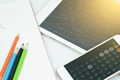 Taschenrechner auf Buch mit Farbbleistift und -tablette Stockbild
