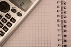 Taschenrechner auf dem Notizbuch Stockfotografie