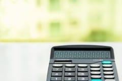 Taschenrechner auf der weißen Tabelle nahe dem Fenster, Seitenansicht der Nahaufnahme lokalisiert Lizenzfreies Stockbild