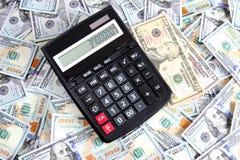 Taschenrechner auf Hintergrund von hundert Dollarscheinen Lizenzfreie Stockfotos