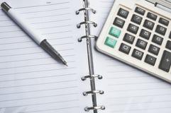Taschenrechner auf Notizbuch mit Stift Stockbilder