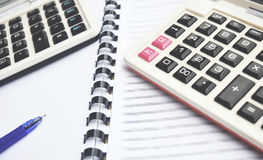 Taschenrechner 2 auf Notizbuch mit Stift Lizenzfreie Stockfotos