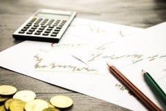 Taschenrechner, Bleistifte und Münzen auf graffica, das Dow Jones auf Devisen vermarkten Lizenzfreies Stockbild