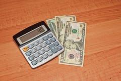 Taschenrechner, der nah auf Banknoten oben liegt Stockfoto