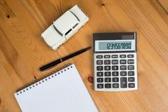 Taschenrechner, ein Stift und ein Spielzeugauto Stockfotos
