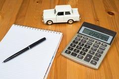 Taschenrechner, ein Stift und ein Spielzeugauto Lizenzfreie Stockfotografie