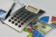Taschenrechner, hundert Dollar und ein Stift, der auf den Diagrammen liegt lizenzfreies stockbild