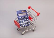 Taschenrechner im Einkaufslaufkatzenwarenkorb finanziell Stockfoto