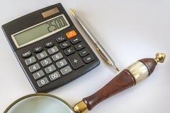 Taschenrechner, Lupe und Kugelschreiber Pen On White Background Lizenzfreie Stockfotos