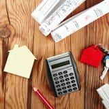 Taschenrechner, Mini House und Skizze auf Holztisch Lizenzfreies Stockfoto