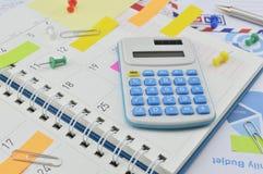 Taschenrechner mit bunten Post-Itanmerkungen über Geschäftstagebuchseite Lizenzfreies Stockbild